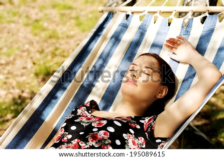 Young woman lying in hammock. - stock photo