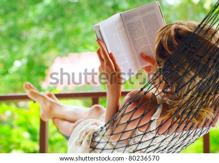 Young woman lying in hammock in a garden and reading a book. Shallow DOF. Focus on a left shoulder - stock photo
