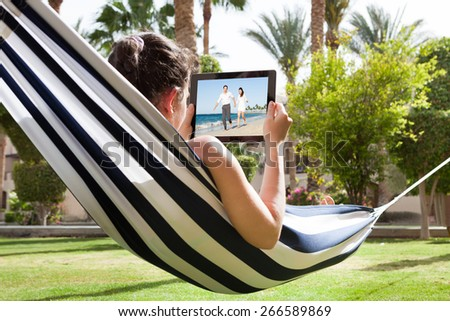 Young Woman Lying In Hammock Watching Video On Digital Tablet - stock photo