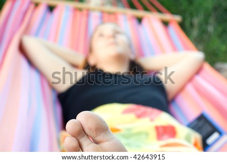 young woman lying in hammock with book and relaxing - stock photo