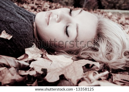 young woman lying in the autumn leaves