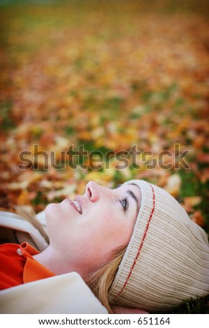 Young woman lying in the fall leaves - stock photo