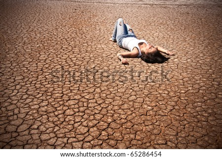 Young woman lying in the middle of a desert. - stock photo