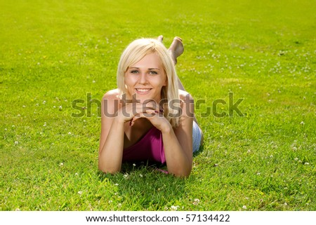Young woman lying in the park on a sunny day - stock photo