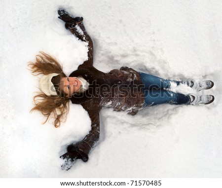 Young woman lying in the snow - stock photo
