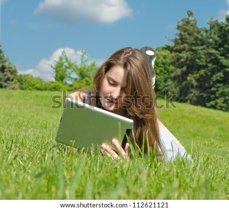 Young woman lying in the sunshine on green grass absorbed in using her touchpad tablet