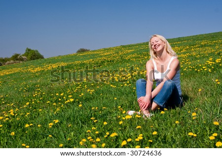 young woman lying on a dandelion meadow