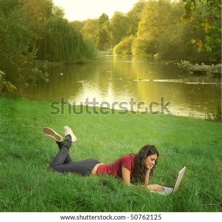 Young woman lying on a green meadow and working on a laptop - stock photo