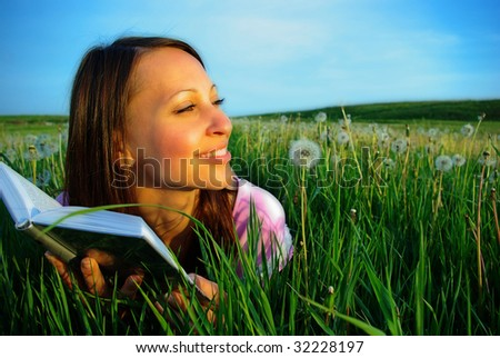 young woman lying on a meadow reads a book - stock photo