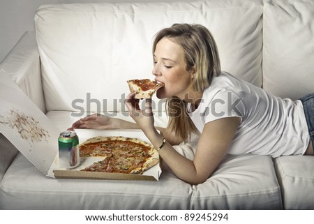 Young woman lying on a sofa and eating pizza - stock photo