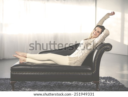Young woman lying on a sofa and stretching. Instagram style - stock photo