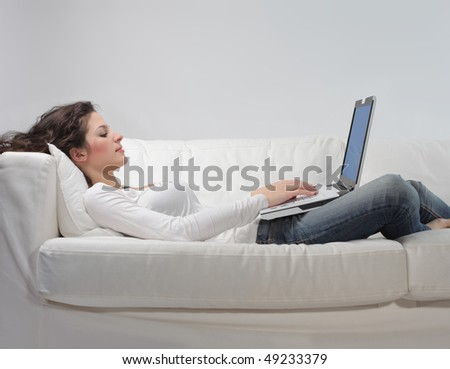 Young woman lying on a sofa and using a laptop