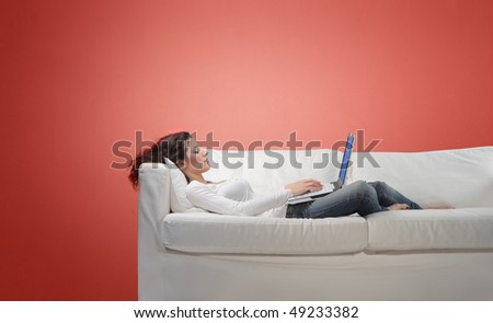 Young woman lying on a sofa and using a laptop - stock photo
