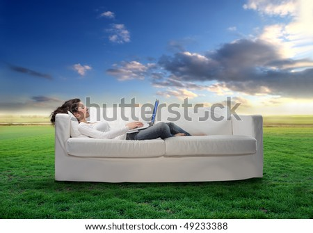 Young woman lying on a sofa and using a laptop with green meadow on the background