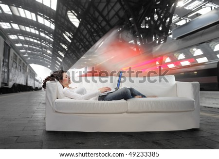 Young woman lying on a sofa and using a laptop with train station on the background - stock photo