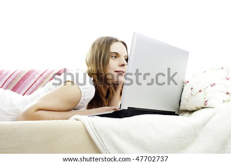 young woman lying on a sofa, working with laptop