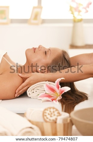 Young woman lying on bed in day spa, enjoying massage with closed eyes.? - stock photo
