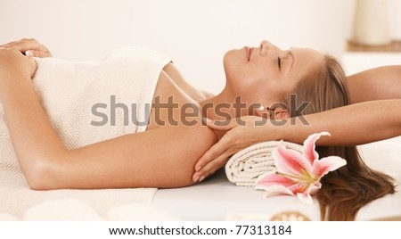 Young woman lying on bed in day spa, enjoying neck massage.? - stock photo