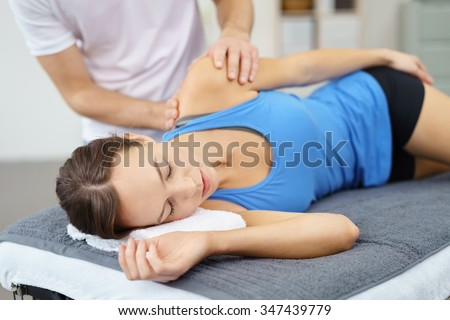 Young Woman Lying on Bed While her Physical Therapist is Giving a Massage to her Injured Shoulder. - stock photo