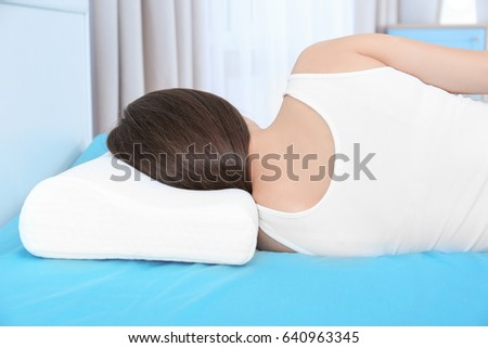 young woman lying on bed with orthopedic pillow at home healthy posture concept