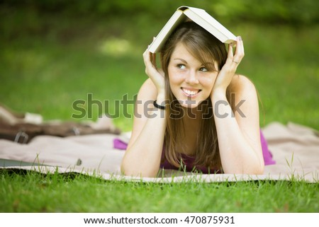 young woman lying on blanket in park and holding a book on her head
