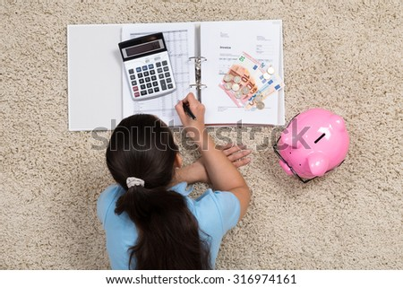 Young Woman Lying On Carpet Doing Calculation At Home - stock photo