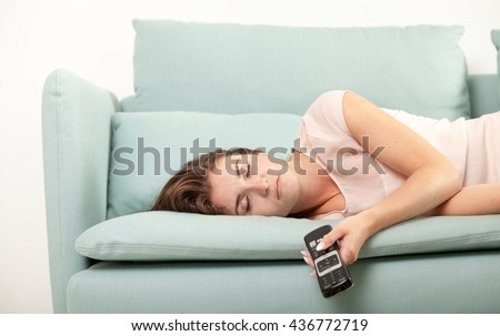 Young woman lying on couch and sleeping with TV remote control, casual style indoor shoot - stock photo