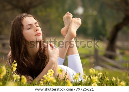 Young woman lying on field dreaming summer day - stock photo