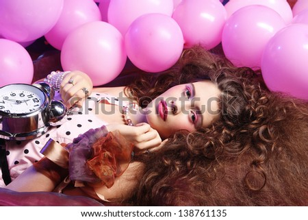 young woman lying on floor among balloons and holding watch - stock photo