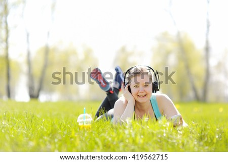 Young woman lying on grass in Park, listening to music on headphones - stock photo