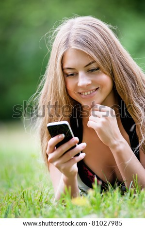 Young woman, lying on grass in park, using her pda - stock photo
