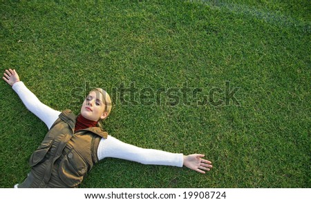 Young woman lying on grass outdoors - stock photo