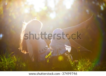 Young woman lying on grass. Sunset backside bright light effect.