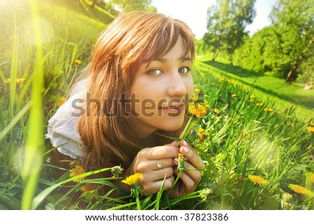 Young woman lying on grass with flowers. Wide angle view.