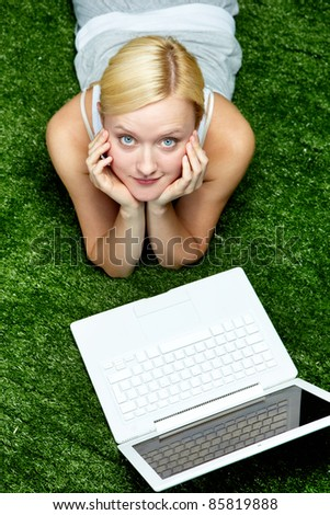 Young woman lying on grass with laptop and looking up - stock photo