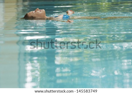 Young woman lying on her back floating in swimming pool