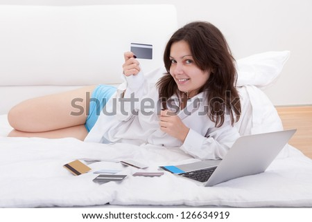 Young woman lying on her bed with a book and open laptop contemplating her numerous credit cards spread out in front of her - stock photo