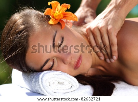 Young woman lying on massage table at spa, outdoors - stock photo