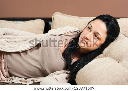 Young woman lying on sofa and thinking,Woman lying on sofa - stock photo