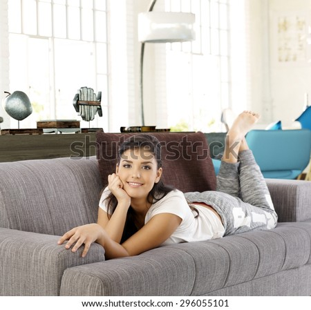 Young woman lying on sofa at home, smiling, looking at camera.