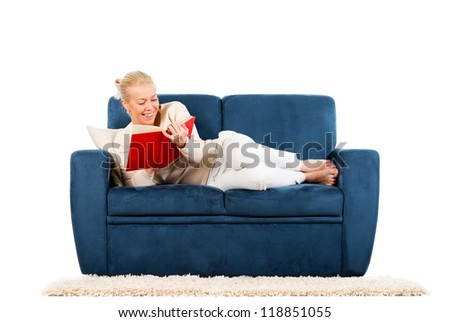Young woman lying on sofa reading a book