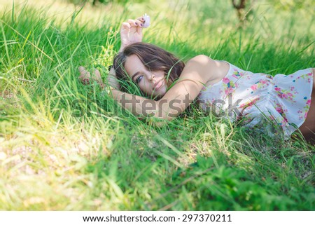 Young woman lying on soft  fresh spring grass daydreaming - stock photo