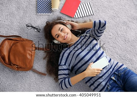 Young woman lying on the floor and listening to music - stock photo