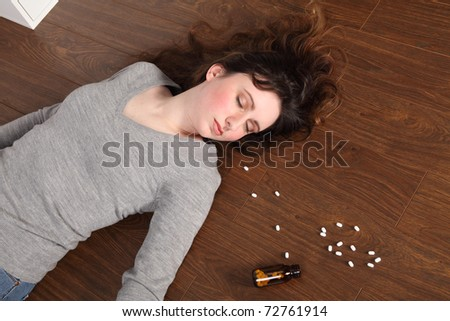 Young woman lying on the floor at home after an overdose of pills. - stock photo