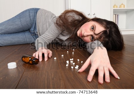 Young woman lying on the floor at home after an overdose of pills. Her eyes are wide open starting straight at camera and there is a bottle of pills on the floor beside her. - stock photo