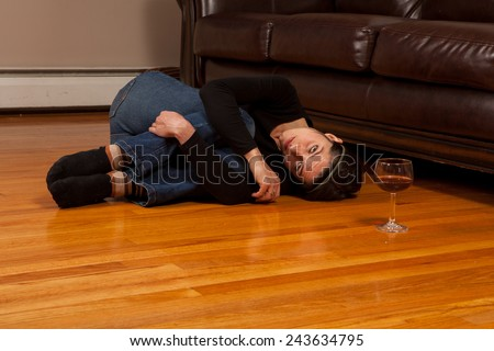 Young woman lying on the floor  in the fetal position with a wine glass looking at the camera - stock photo