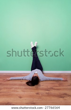 Young woman lying on the floor with her feet up the wall, plenty of copy space to add text, frame or even a TV. - stock photo