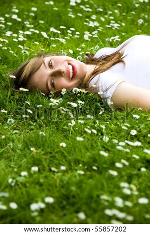 Young woman lying on the grass - stock photo