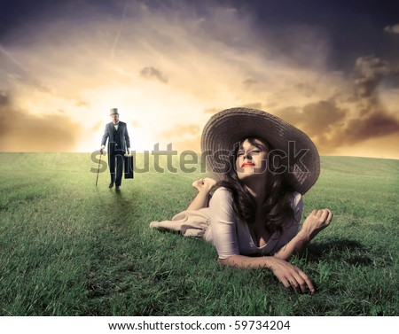 Young woman lying on the grass and gentleman walking - stock photo