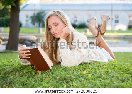 Young woman lying on the grass and reading a book, dressed in white sweater and shorts.  - stock photo